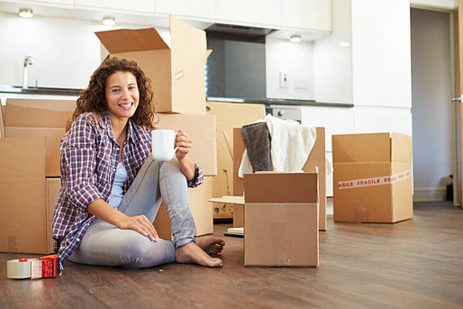 Picture of a young woman unboxing in her new apartment and drinking coffee