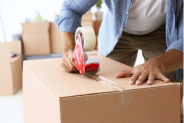 Picture of a House moving concept. Closeup of man packing cardboard box