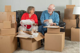Picture of Adult Senior Couple Packing or Unpacking Moving Boxes in their home